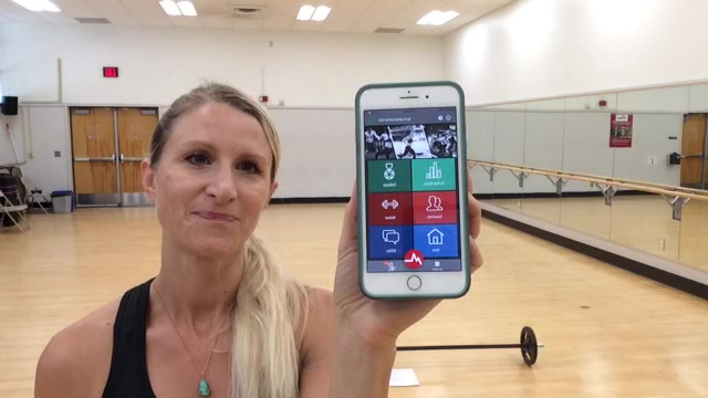 Woman in class using fitness app to record her heart rate.